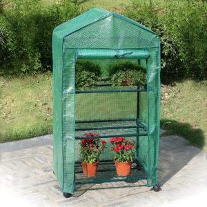 Kleines Gewächshaus mit Folienbezug und grünen Pflanzen drin